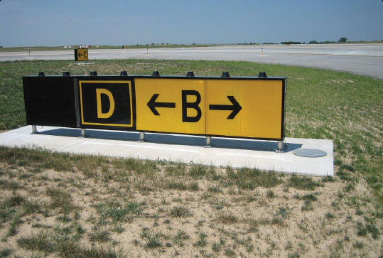 Figure 14-18. Taxiway Bravo direction sign with a collocated Taxiway Delta location sign. When the arrow on the direction sign indicates a turn, the sign is located prior to the intersection.