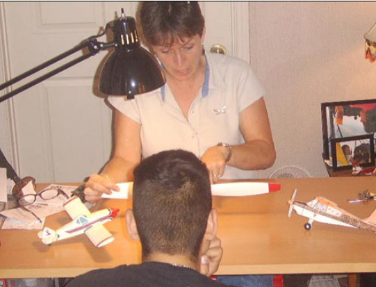 Figure 3-1. An aviation instructor communicates with her student using model airplanes to ensure the student's understanding of the principles discussed.