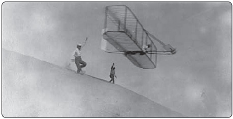 Figure 1-4. Orville Wright (left) and Dan Tate (right) launching the Wright 1902 glider off the east slope of the Big Hill, Kill Devil Hills, North Carolina on October 17, 1902. Wilbur Wright is flying the glider.