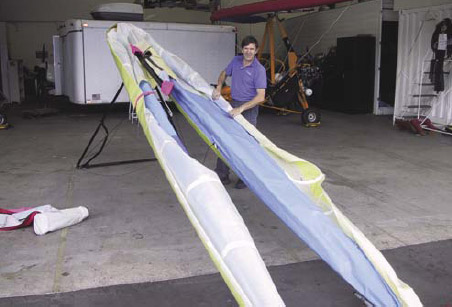 Figure 5-35. Left hand side rolled up and secured with wing tie. Rolling right hand sail which will also be secured with wing tie.