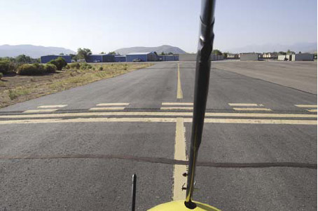 """Figure 5-66. Taxi on the airport yellow taxi line, but stop at the """"hold short line"""" to get clearance before taxiing across or onto an active airport runway."""