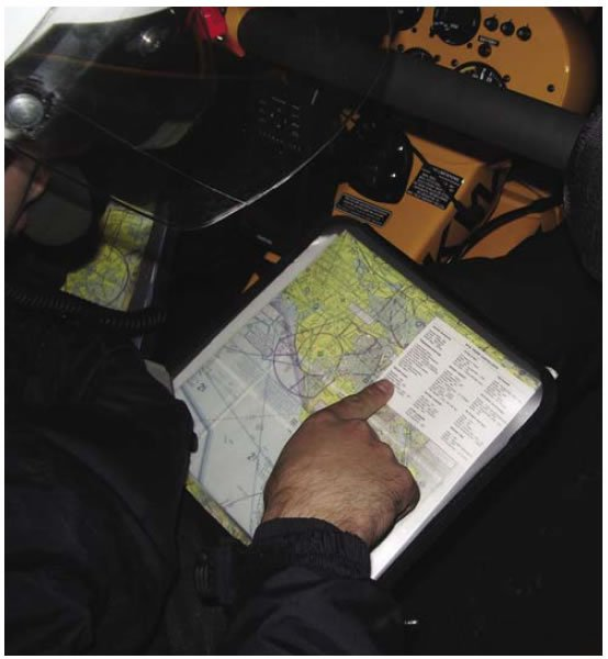 Figure 12-8. Reviewing before-takeoff checklist, which is included for the flight with the sectional charts on the kneeboard.